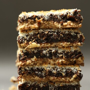 A close up image of a stack of chocolate, prune and coconut squares