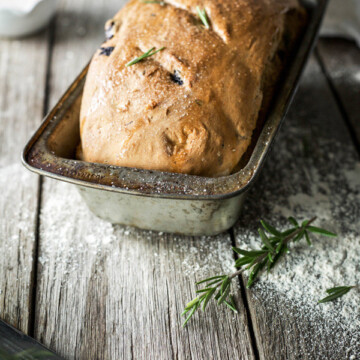 A homemade loaf of bread in a vintage bread pan on a wooden bench