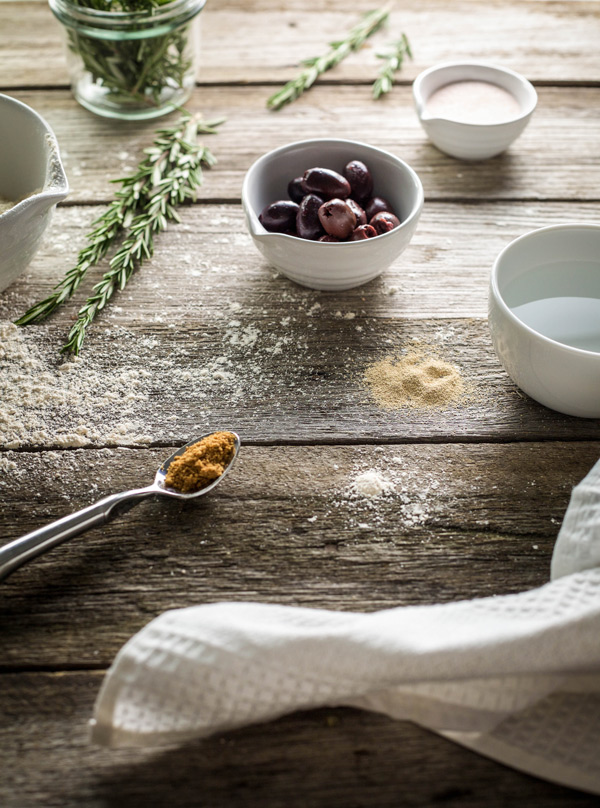 Olive bread ingredients laid out on a wooden table top