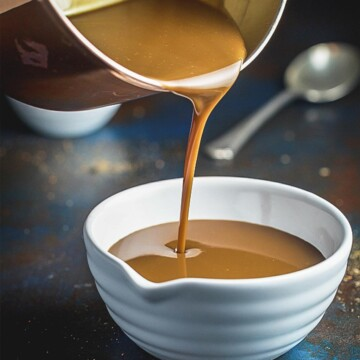 A front on image of caramel sauce being poured from a saucepan in to a white bowl