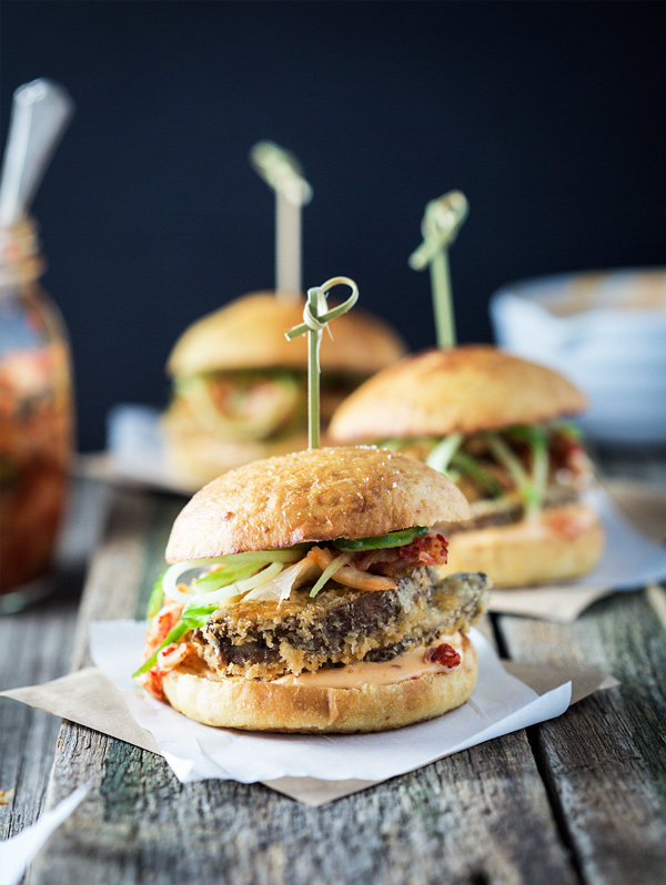 Three vegan kimchi crispy mushroom burgers with one close-up on a rustic wooden table.