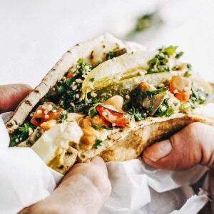 A man's hands holding a stuffed pita in sandwich paper.