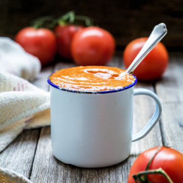 Homemade ketchup in a white metal cup with tomatoes around