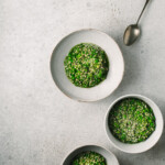 Three bowls of green buckwheat risotto on a grey background