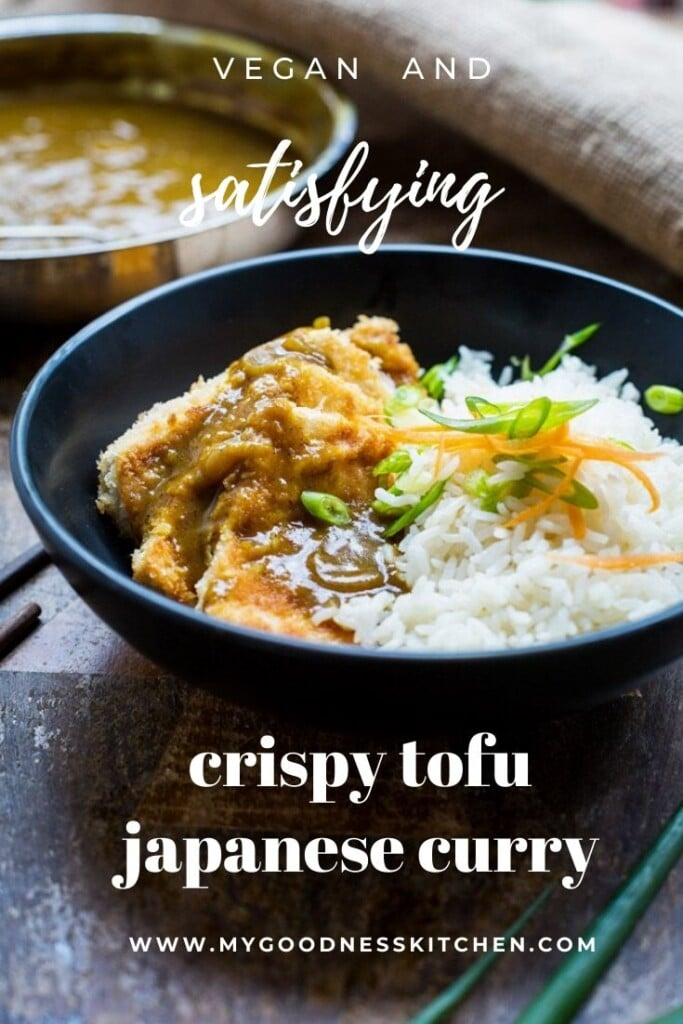 Front on image of a black bowl full of japanese tofu curry with steamed rice sitting on a rustic wooden board