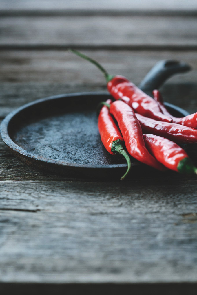 a small pile of red chillies on a cast iron pan resting on a rustic wooden table