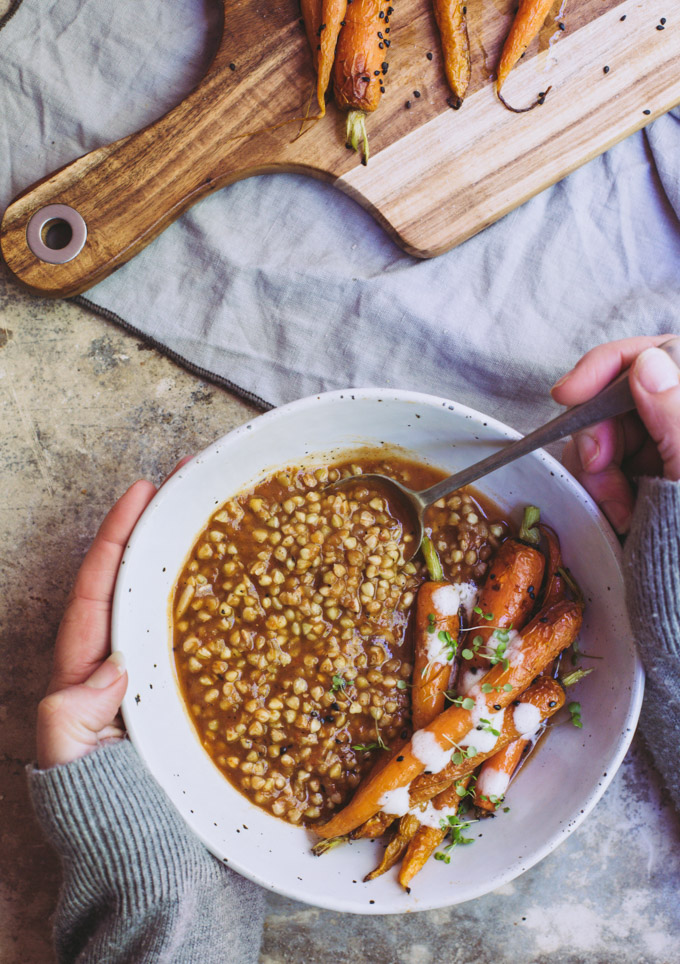 overhead image of a woman's hands holding a bowl of smoky eggplant buckwheat with roasted carrots