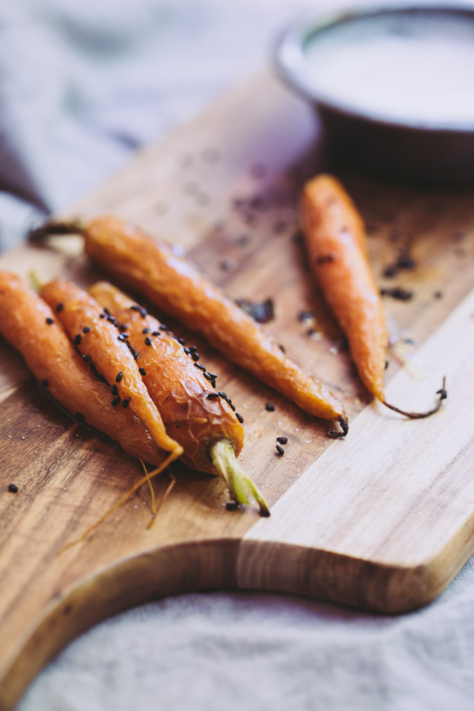 close up image of roasted carrots with sesame seeds and a white dipping sauce