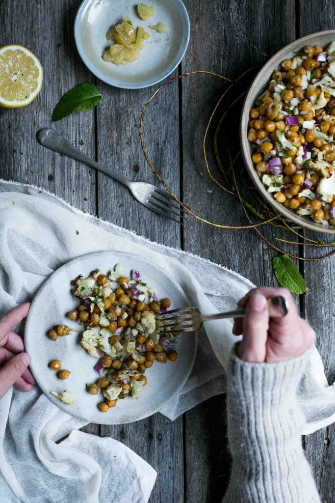 An overhead image of a woman scooping a mouthful of chickpea salad on to a fork