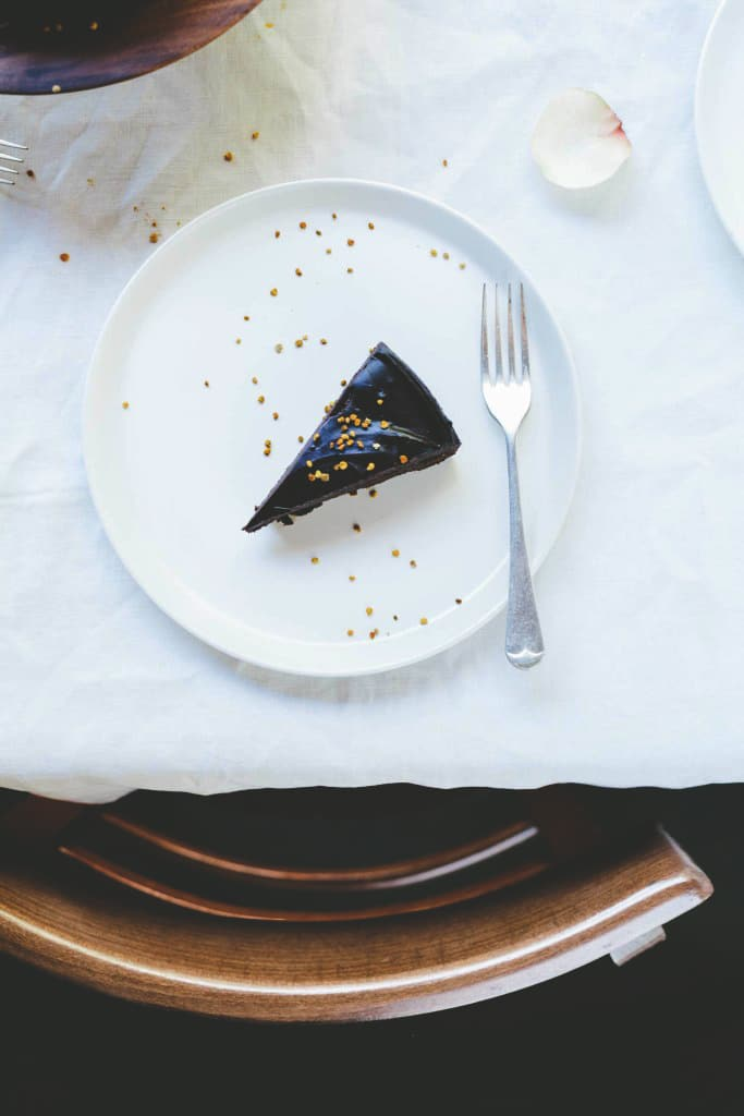 A piece of raw chocolate cake on a white plate on a table with a white cloth