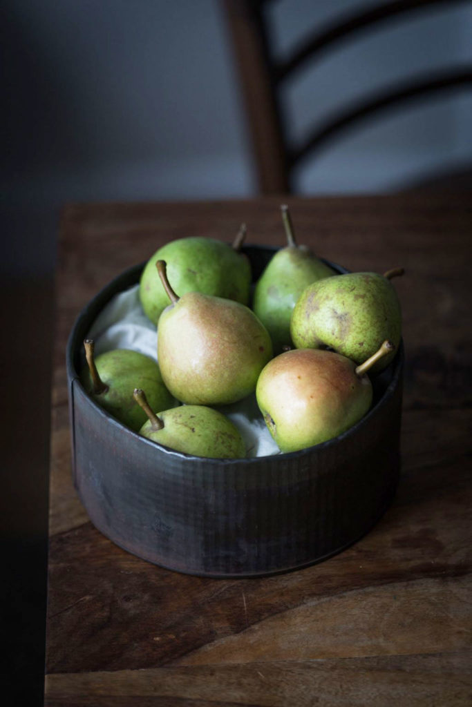 An 45 degree angled image of a vintage tin bowl full of ripe pears sitting on a wooden table with a wooden chair in the background