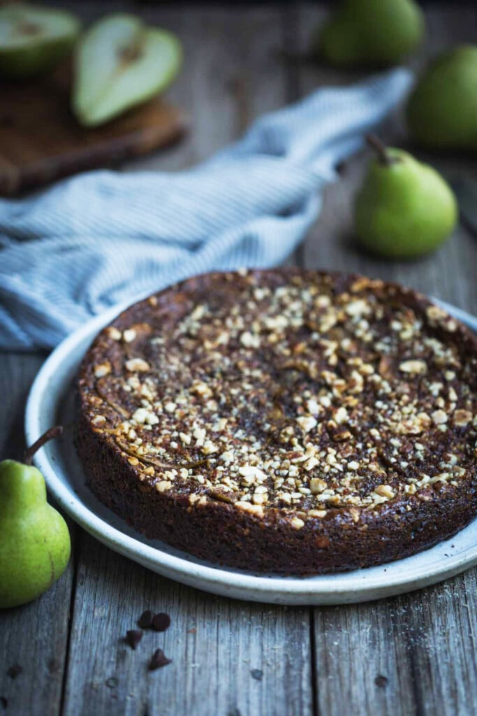 A shot of the finished flourless chocolate pear cake sitting on a white plate on a rustic wooden table with whole and cut pears in the background.