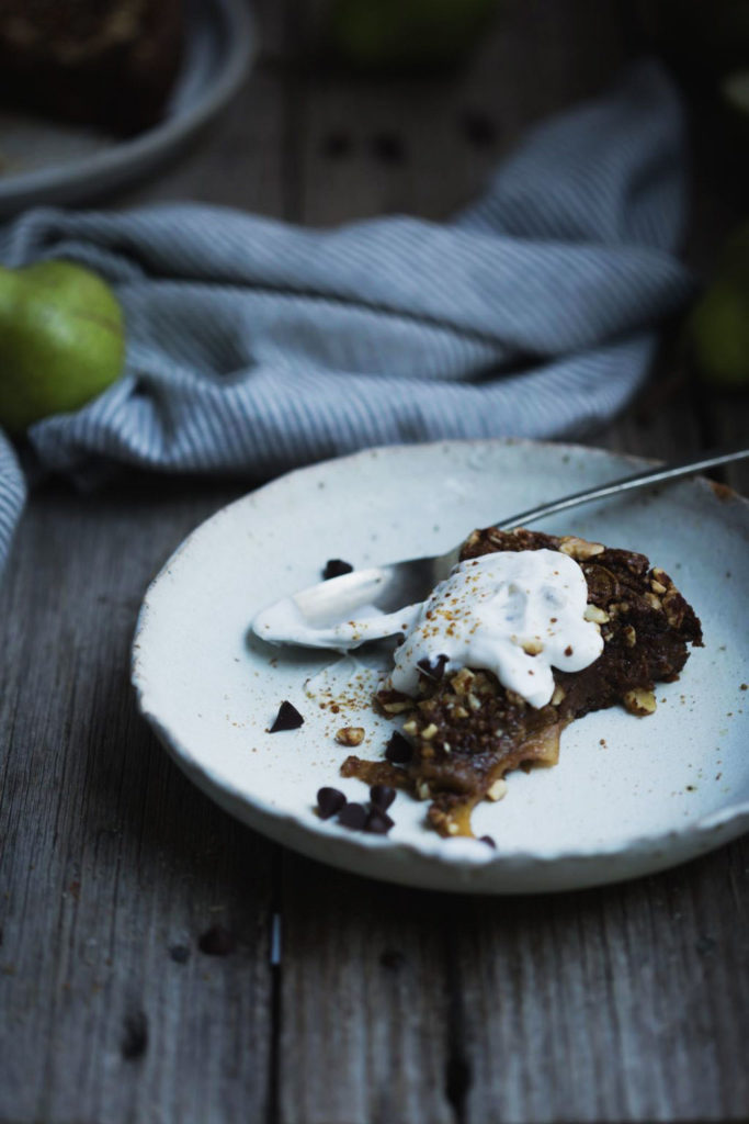 A cut slice of flourless chocolate pear cake with a dollop of coconut yoghurt in an stoneware white bowl on a rustic wooden table