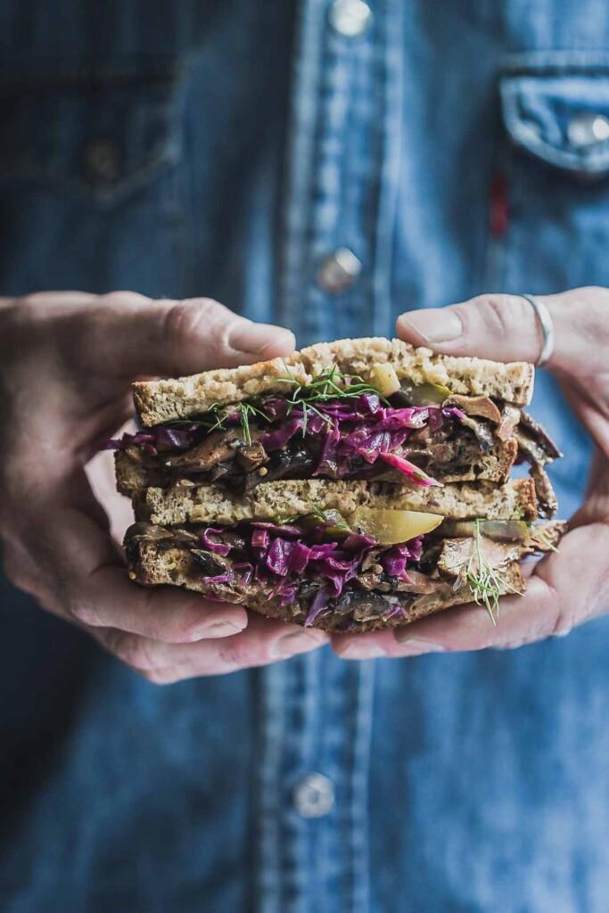 man holding vegan Reuben sandwich