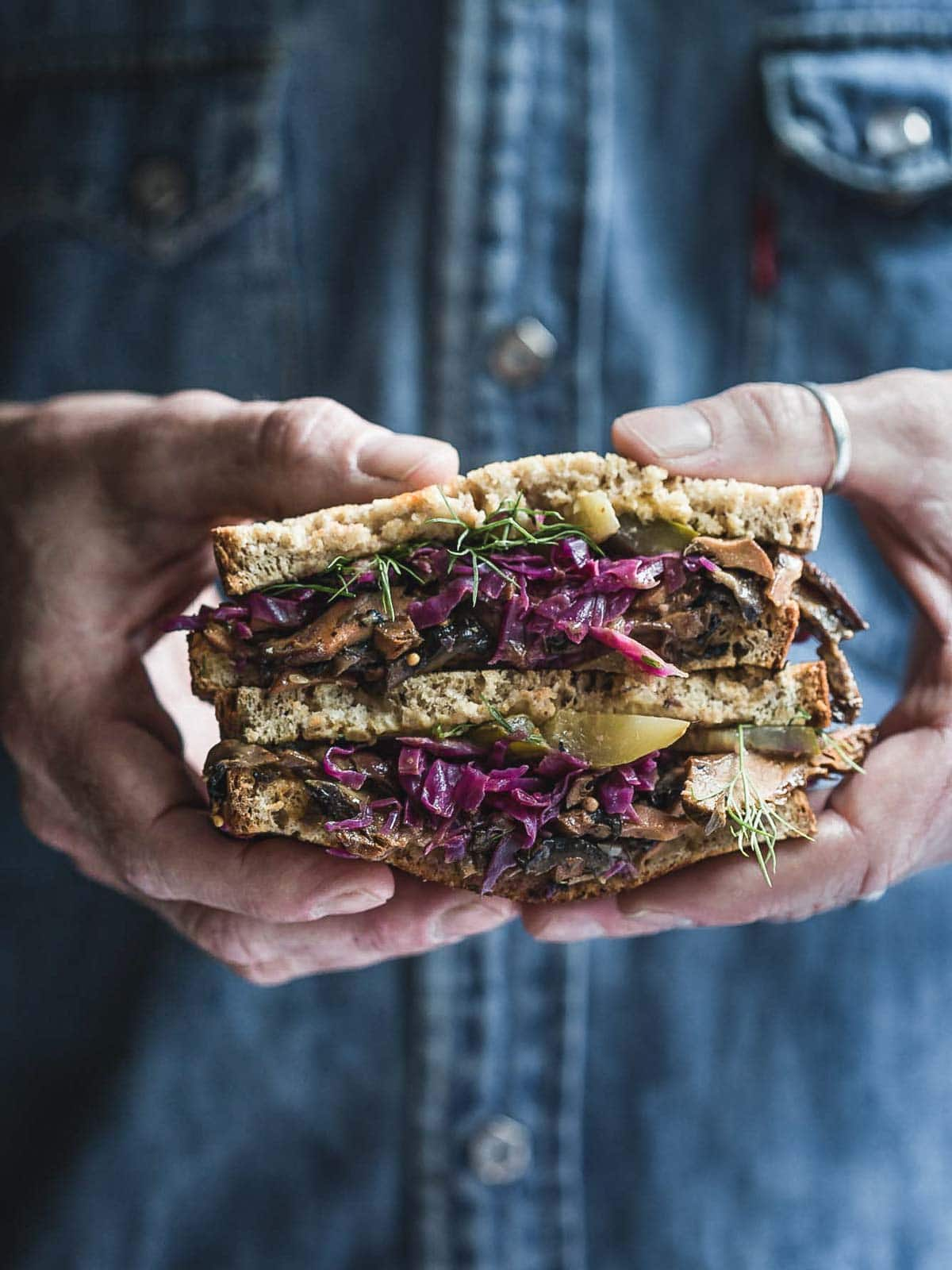 A man holding a Reuben Sandwich.