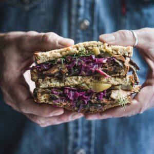 Hands holding a Reuben Sandwich.