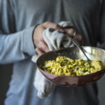 An image of a man holding a skillet of scrambled tofu
