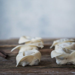 Rows of folded wontons on a wooden board before cooking.