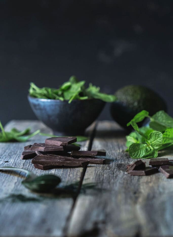 Front on image of smoothie ingredients including a stack chunky stack of dark chocolate in the foreground and fresh mint on a rustic wooden bench.