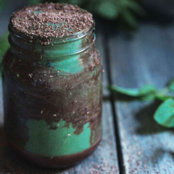 A close up of a jar of chocolate and mint smoothie with mint leaves
