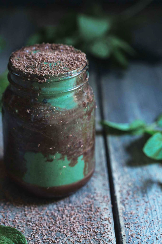 A close-up front on image of a large jar of the finished dairy-free chocolate mint smooth with chocolate ripples and dark chocolate shaving on top sitting on a rustic wooden bench with fresh mint scattered around
