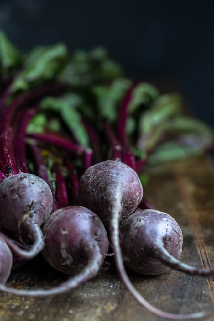 Front angle close-up image of freshly washed beets on a wooden chopping board