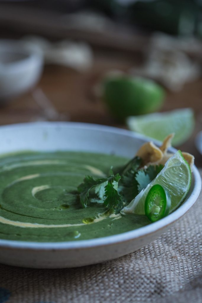 Cheesy Jalapeño Broccoli Soup is a vibrant mix of spicy broccoli soup with a cheesy cashew cream, topped with fresh coriander, lime and corn chips. (v)