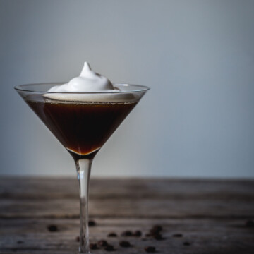 An espresso martini with marshmallow fluff on a wooden table with coffee beans.
