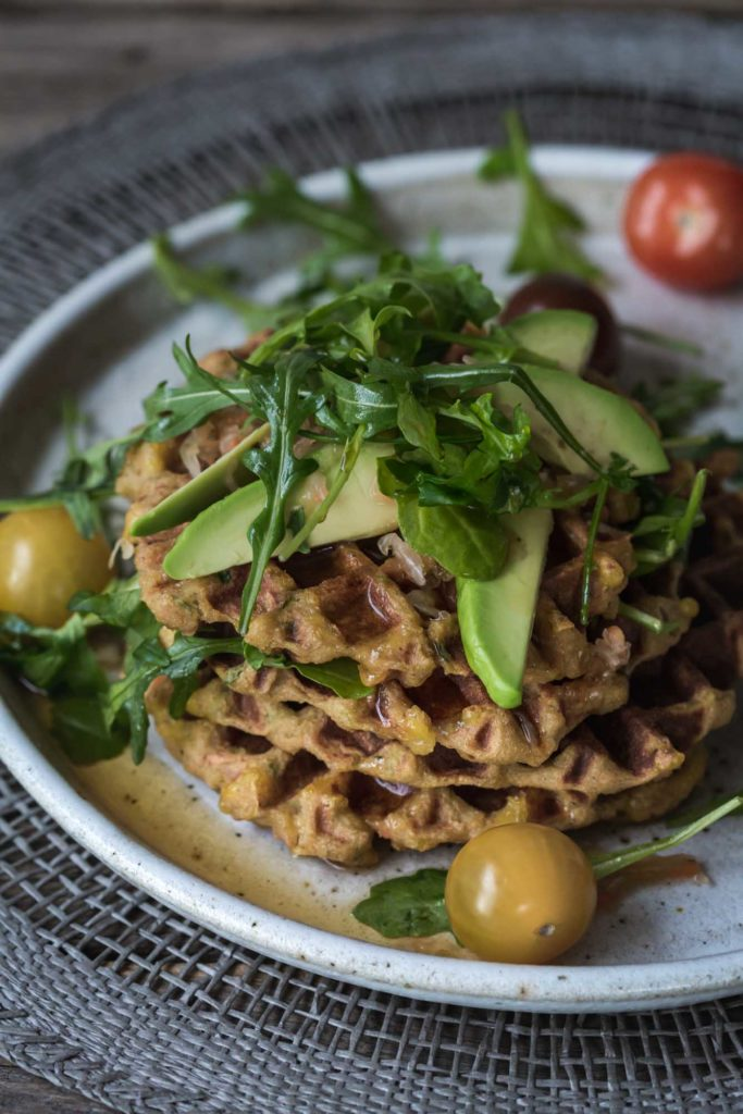 A plate of savoury waffles on a plate with avocado and tomatoes.