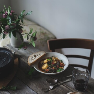 Potato and lentil stew in a white bowl on a rustic table setting.
