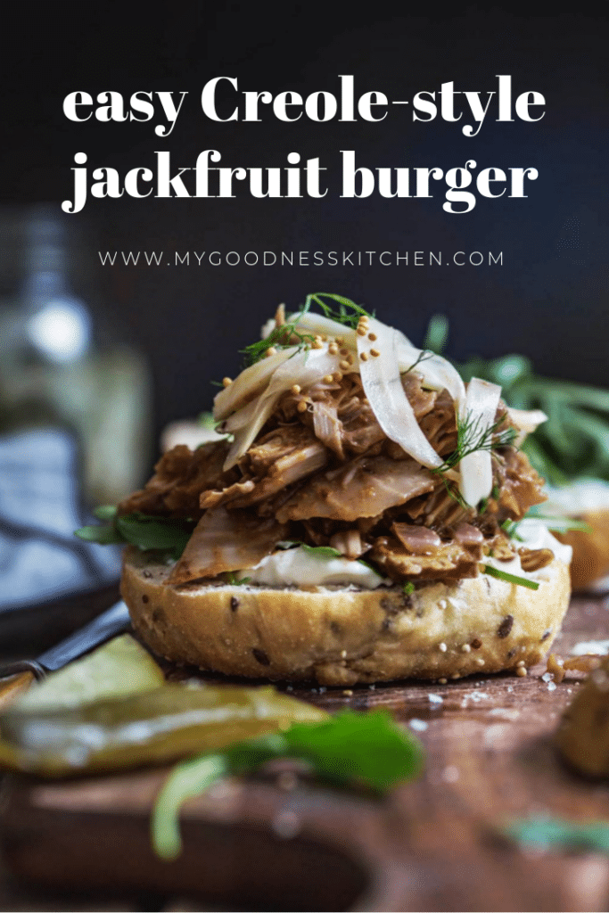 front on image of easy Creole jackfruit burger without it's bun top sitting on a wooden board with pickles in the foreground. Title text overlay in white