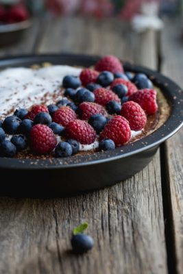 a close up image of a vegan chocolate pie with fresh berries and coconut cream