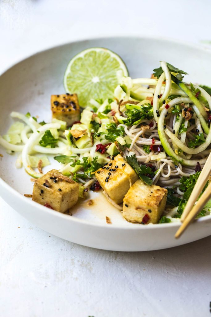 Soba noodles entwined with zucchini noodles, massaged kale leaves, crispy tofu and a spicy lemongrass dressing combine in this Crispy Tofu Lemongrass Bowl.