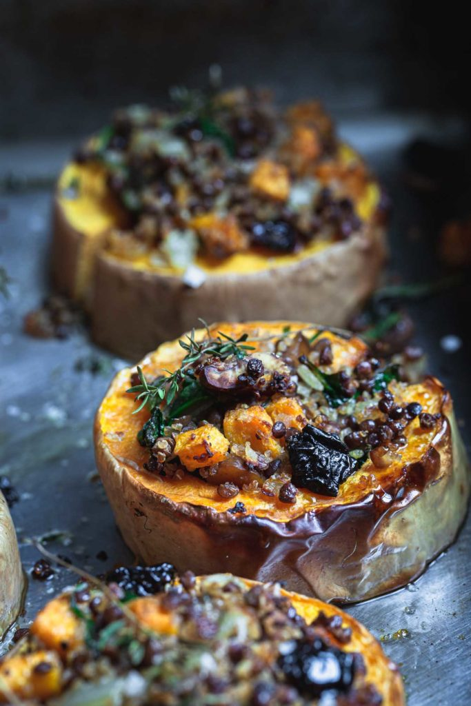 A close-up front on image of holiday stuffed squash rounds freshly cooked on a roasting tray