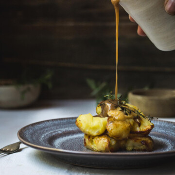 A plate of roast potatoes with gravy being poured.