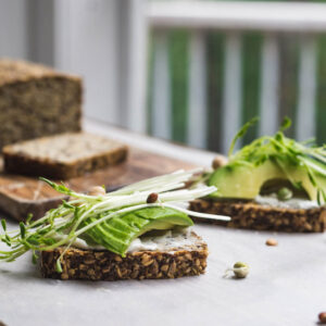 Sliced seeded bread topped with avocado and greens on a white background.