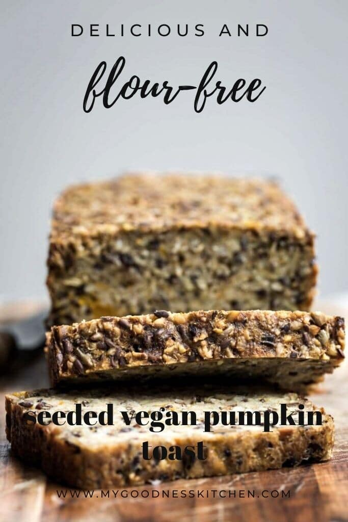 A close up image of vegan seeded pumpkin bread loaf sliced on a wooden board