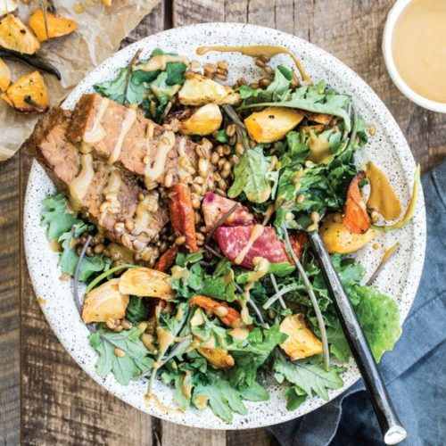 An overhead image of a green salad with tempeh in a white bowl.