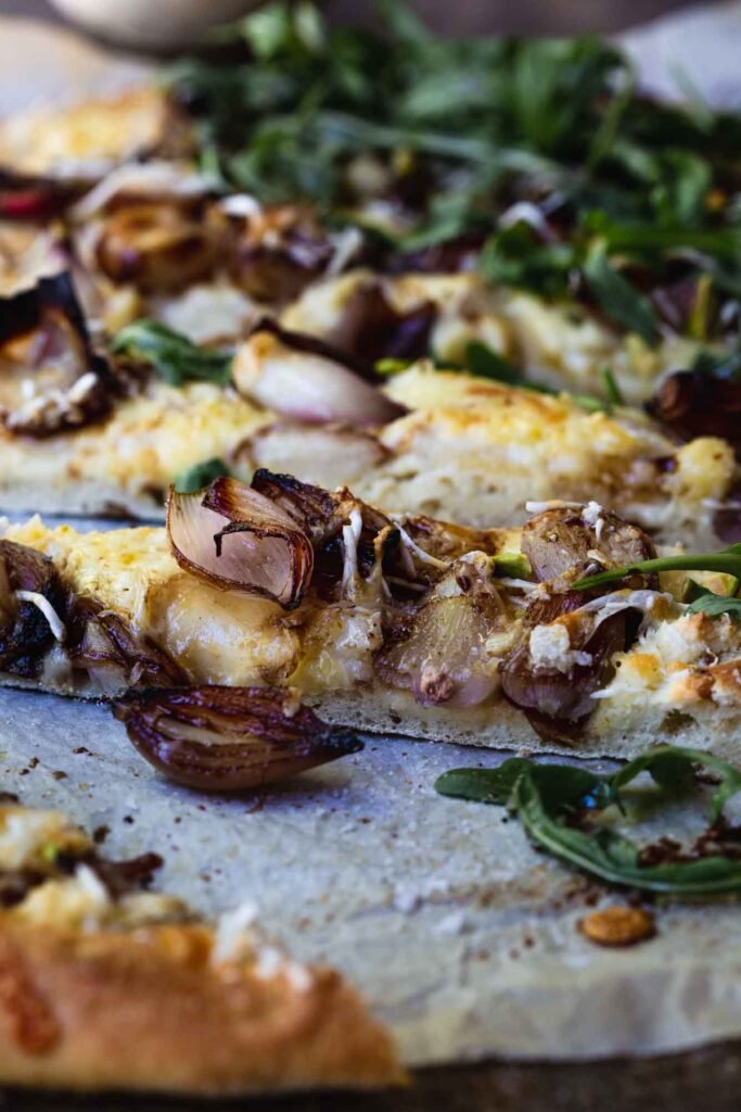 A close up image of a vegan white pizza with pears and balsamic shallots on textured baking paper