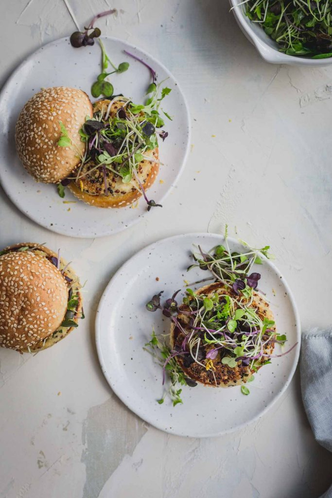a flat lay image of 3 crispy quinoa cauliflower burgers on a marbled surface