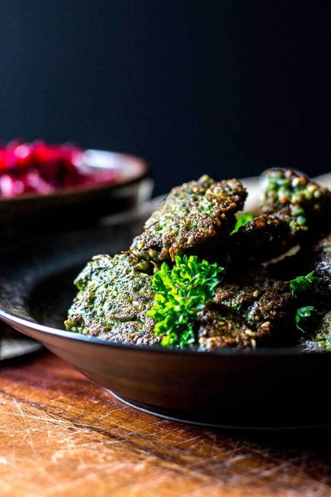 A black bowl full of broad bean falafel with tahini dressing