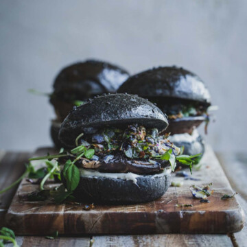 Three mushroom burgers on a wooden board.