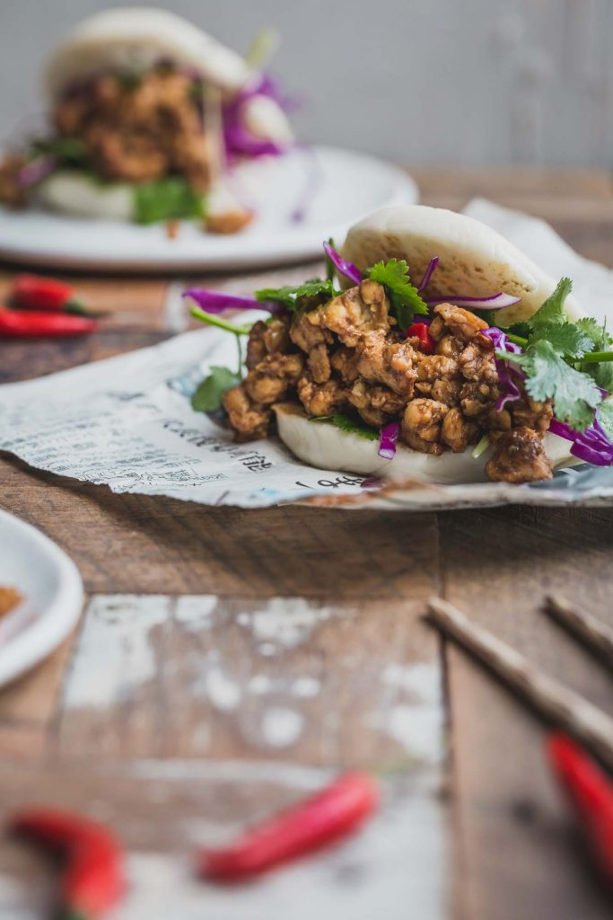 Close up image of a bao bun filled with peking tempeh and greens sitting on a sheet of Asian newspaper. Another bun sits on plate in the background. A pair of chopsticks in the foreground on a rustic wooden table.