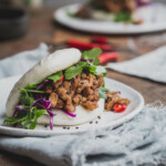 A close up image of a bao bun filled with tempeh and greens on a wooden table.