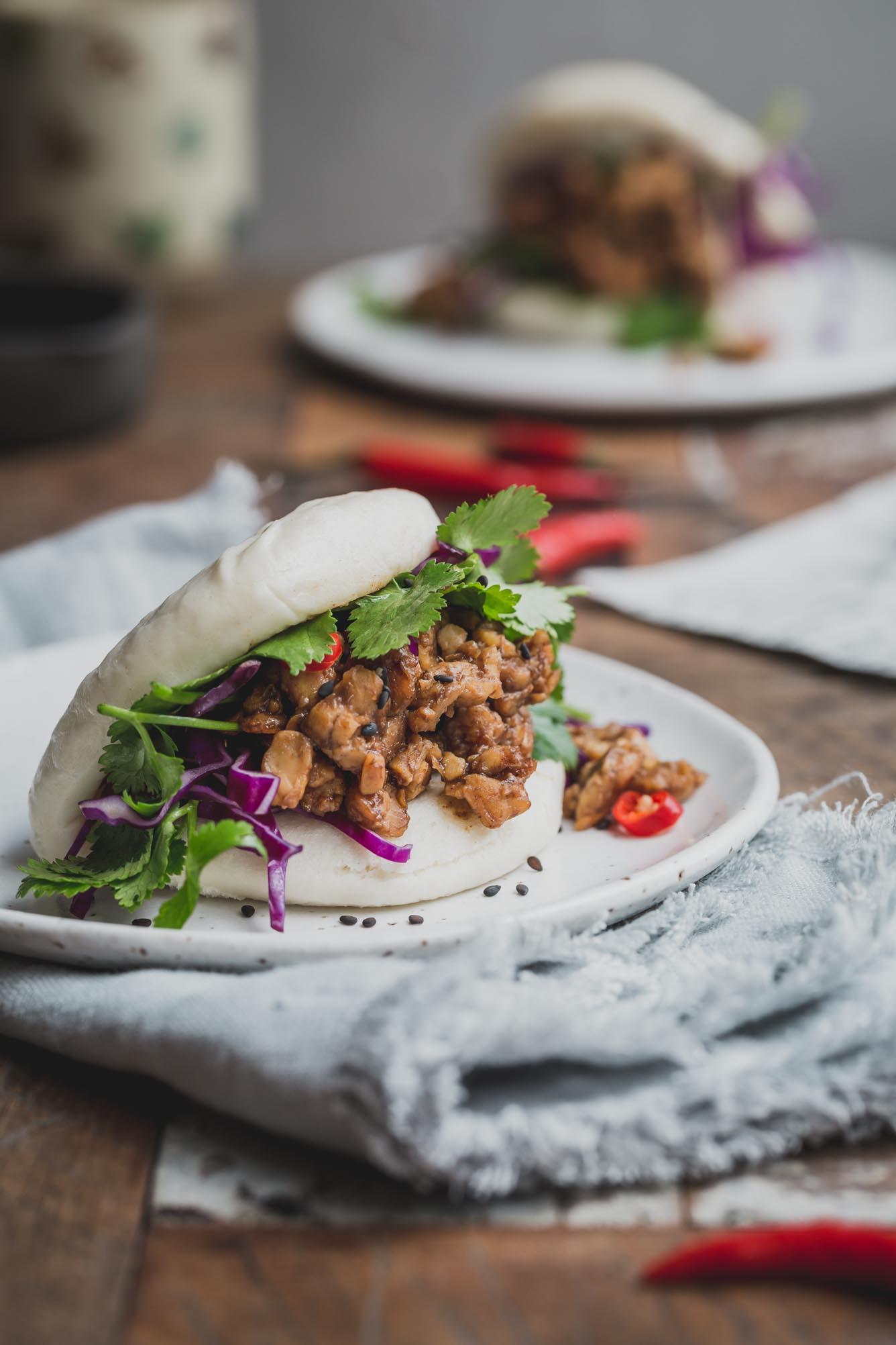 A bao bun with fresh herbs on a white plate.
