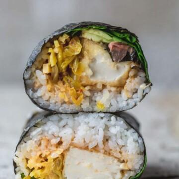 A close up of a sushi burrito on a board