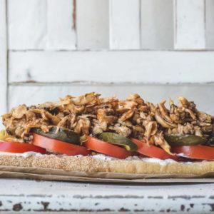 A vegan pulled mushroom sandwich on a wooden char