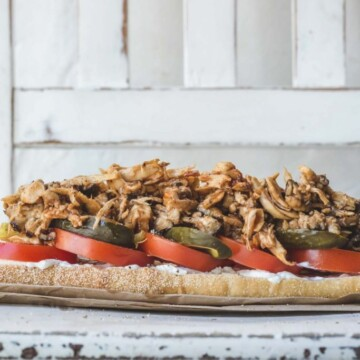 A vegan pulled mushroom sandwich on a wooden chair