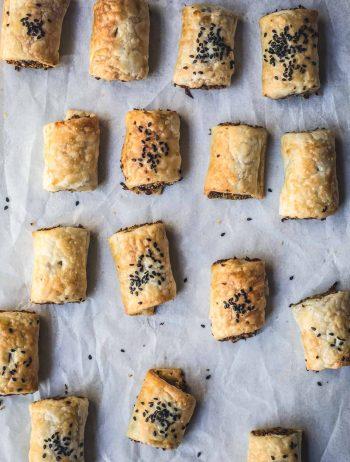 flat-lay image of cut vegan sausage rolls on baking tray