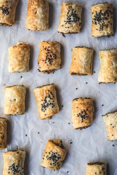 flat-lay image of cut vegan sausage rolls on baking tray